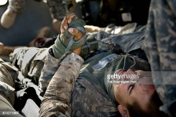 Two wounded US soldiers join hands while being transported to Kandahar Airbase Hospital after suffering lower leg injuries from an IED blast to their...