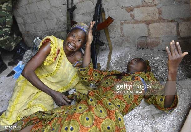 Two wounded women are pictured after a grenade was thrown at the Kokoro market in the Km 5 district of Bangui on January 5 2014 The number of people...