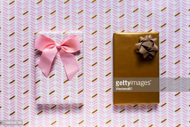 two wrapped gifts against wrapping paper background - 襟元の服飾品 ストックフォトと画像