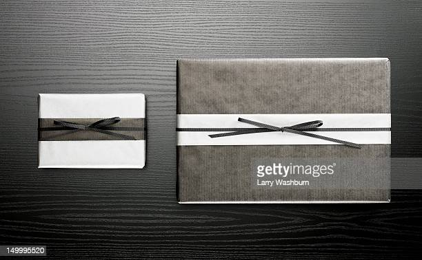 Two wrapped presents on a wooden table
