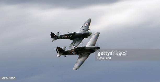 Two WWII vintage fighters a Spitfire and a Hawker Hurricane perform over the airfield during the 'Warbirds over Wanaka' International Airshow on...
