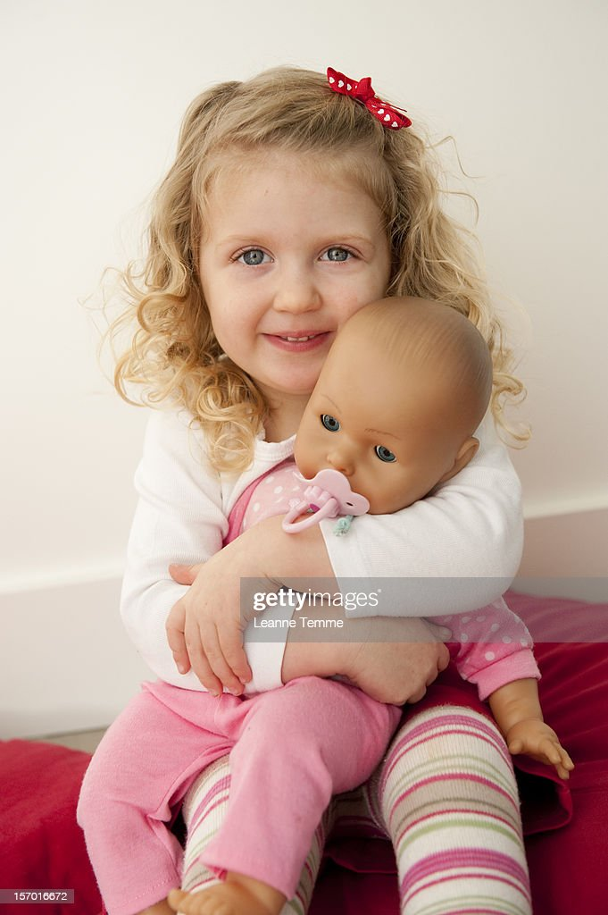 two year old blonde girl nursing a baby doll stock photo getty images. Black Bedroom Furniture Sets. Home Design Ideas