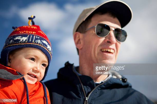 A two year old boy is held by his grandfather, an active senior, on a blue sky day in the mountains of Colorado.