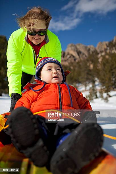 A two year old boy is pushed on a sled by his grandma in the mountains of Colorado.