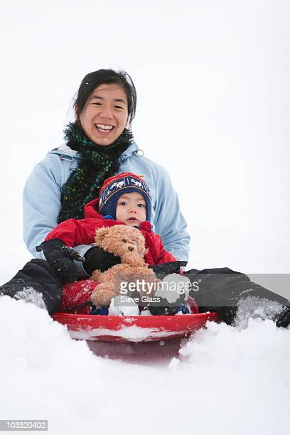 a two year old boy, sleds with his mother and his teddy bear at the local sledding hill in fort collins, colorado. - tobogganing stock pictures, royalty-free photos & images
