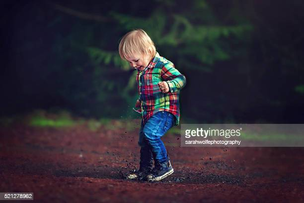 two year old boy stomping in a mud puddle