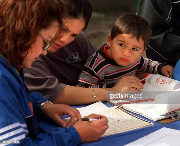 Two year old Fernando Gonzalez watches as census worker Norman Gonzalez assists his family fill out their census forms that they received in the mail...