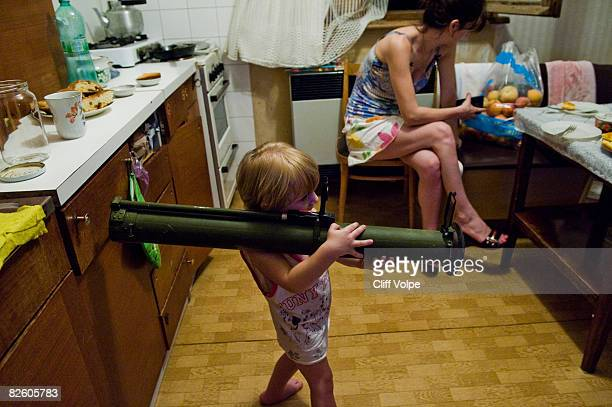 Two year old Georgian toddler plays with an empty Russian made RPG-26 rocket launcher that was found by a villager abandoned in the conflict zone on...