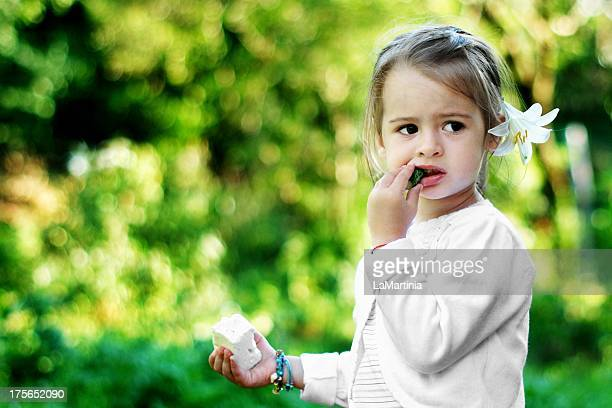 Two year old girl eating cucumber and white cheese