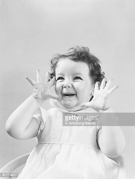 Two year old girl holding hands up to face, with surprised expression, portrait.