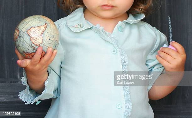 Two year old girl holding small globe
