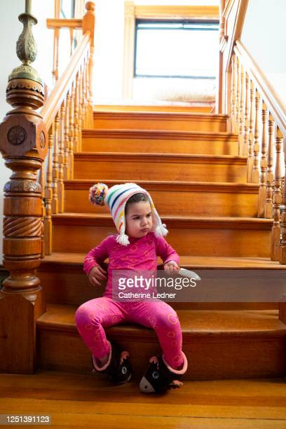 two year old girl in pj's and winter hat and booties holding a popsicle and making a funny face - catherine ledner stock pictures, royalty-free photos & images