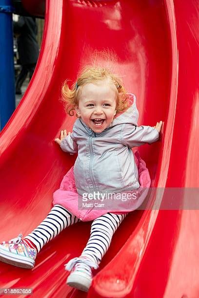 two year old girl on slide in playground