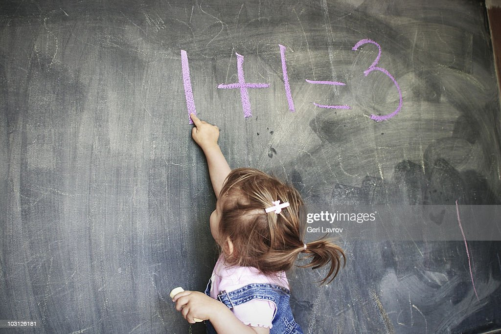Two year old girl pointing at a blackboard : Stock Photo