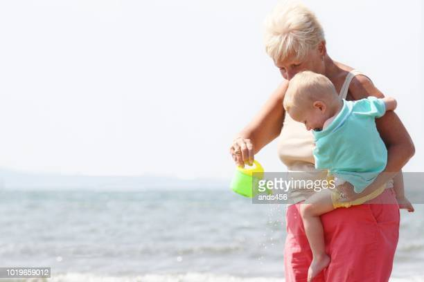 two year old little boy and his grandmother at beach - british granny stock photos and pictures