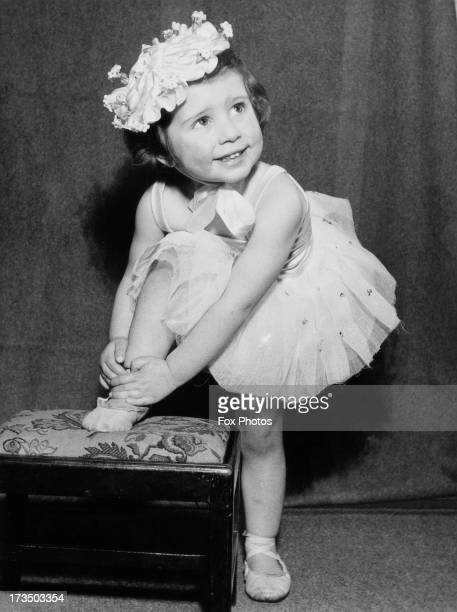 Two year-old aspiring ballerina Rosemary Hoffman ties her shoe before ballet practice near her home in Teddington, London, 28th February 1953.