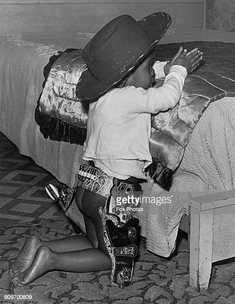 Two yearold Clarence James Jones says his prayers at bedtime dressed in a cowboy outfit February 1957 He is the son of a US Army staff sergeant