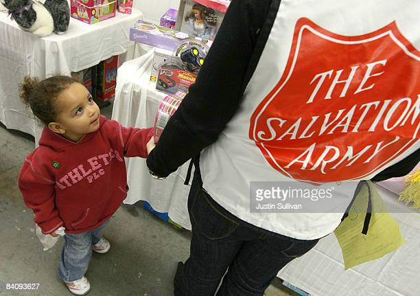 Two yearold Vanessa Rivas picks out toys with a Salvation Army volunteer during a food and toy giveaway to families in need December 19 2008 at the...