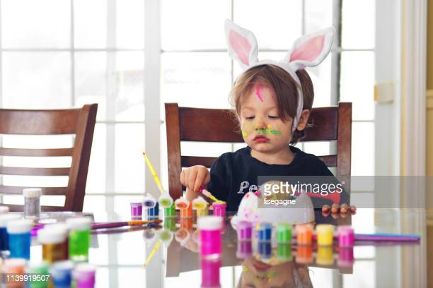 two years little boy painting easter eggs - dirty easter stock pictures, royalty-free photos & images