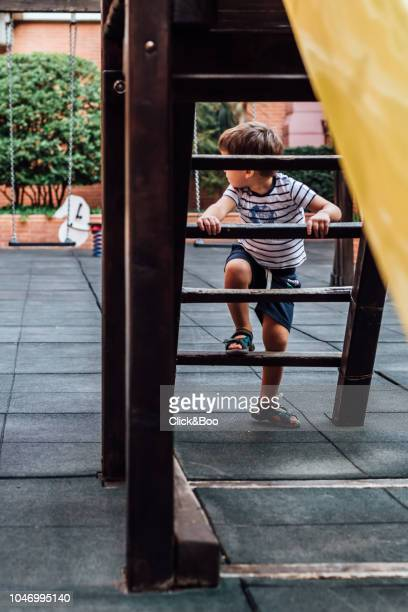 Two years old child climbing the stairs of a yellow slide (outdoors)