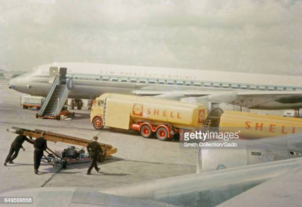 Two yellow and red Shell brand gasoline trucks refuel a KLM Royal Dutch Airlines airplane on the tarmac at an airport, as three men roll a luggage...
