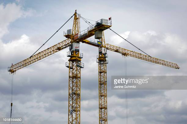 BERLIN GERMANY AUGUST Two yellow cranes for house construction are pictured in front of a cloudy dramatic sky on August 10 2018 in Berlin Germany