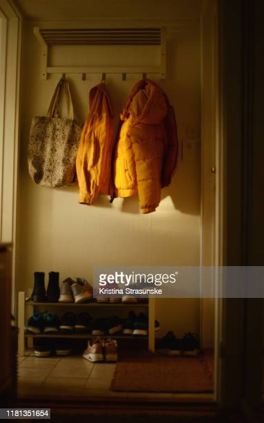 two yellow jackets and a tote bags hanging on a rack over a shoe shelf - jaqueta - fotografias e filmes do acervo