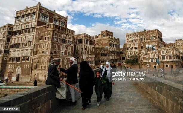 Two Yemeni men sit and talk by the ledge of a bridge as another woman and two girls pass by next to them with the UNESCOlisted buildings of the old...