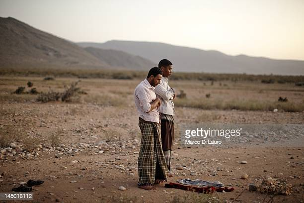 Two Yemeni pray at sunset on March 11 2011 in Socotra Island Yemen The Socotran Archipelago is one of the greatest treasures of biodiversity Located...