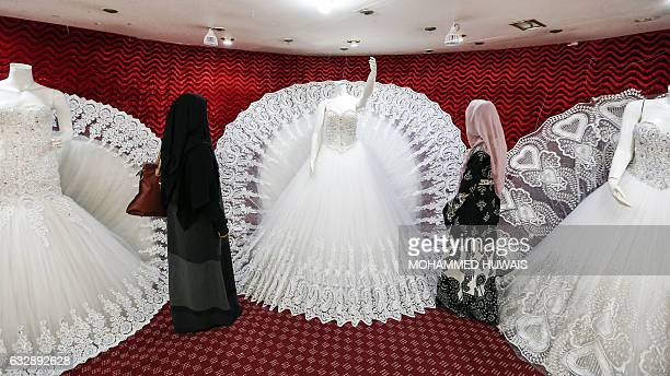 Two Yemeni women one clad in a facecovering burqa browse through wedding dresses in a shop in the capital Sanaa on January 28 2017 Despite the...