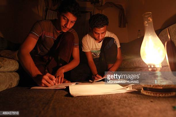 Two Yemeni youths review their studies for the final exams on the light of an oil lamp in Sanaa late on June 10 2014 Yemen suffered a total blackout...