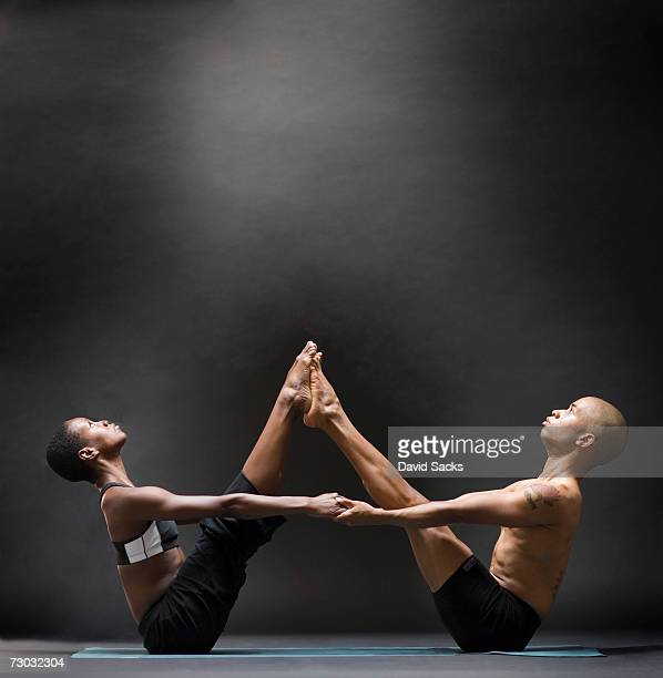 Two yoga students balancing in symmetric pose, side view