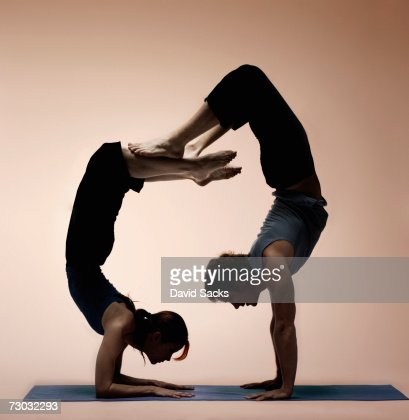two yoga students in difficult poses balancing on one