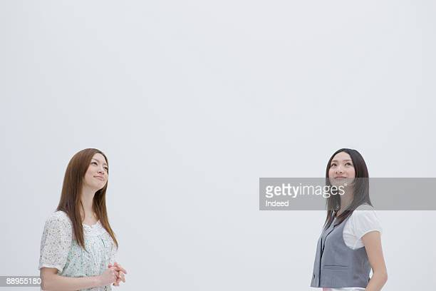 Two youn women looking up, smiling
