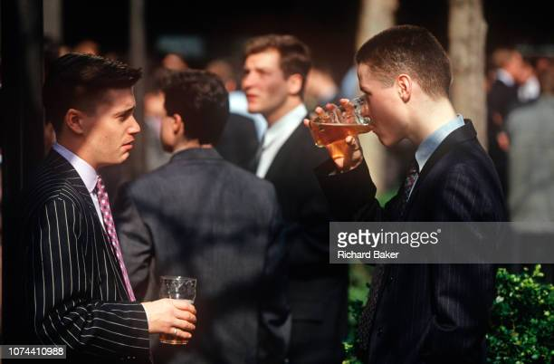Two young 1990s city workers drink pints of beer outside a pub in the City of London the capital's financial centre on 20th May 1993 in London England