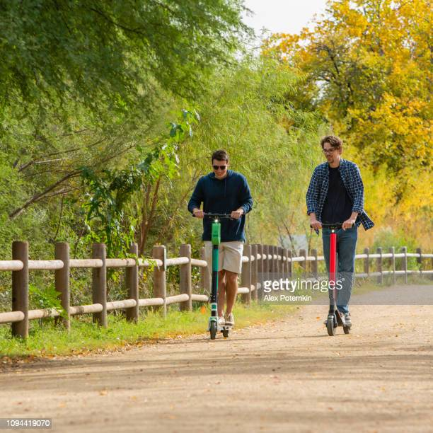 two young, about 30-years-old, male friends, latino, and caucasian white, riding the rental electrical scooter in the colorful autumn park. - alex potemkin or krakozawr latino fitness stock photos and pictures