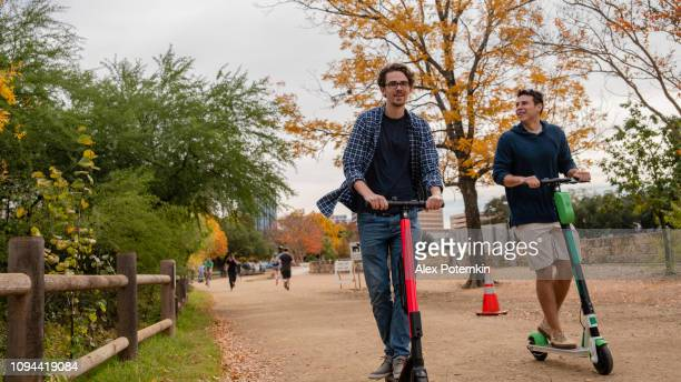two young, about 30-years-old, male friends, latino, and caucasian white, riding the rental electrical scooter in the colorful autumn park. - mobility scooter stock photos and pictures