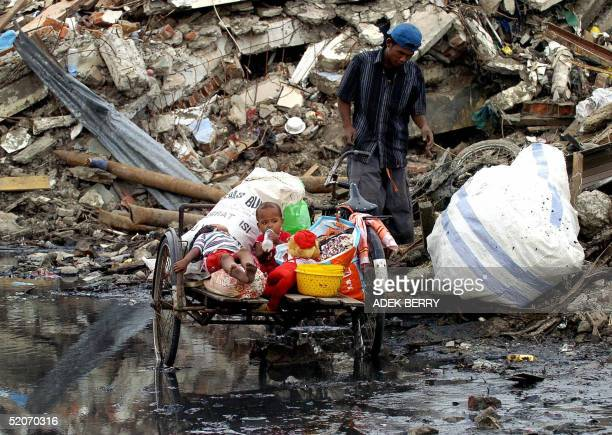 Two young Acehnese children await their father who scavenges among piles of debris for useable items, 27 January 2005, left by last month's tsunami...