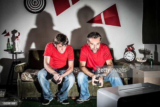 Two young adult brothers videogamer playing at night