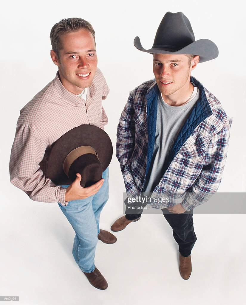 two young adult caucasian cowboys wearing boots are standing beside each other one holding a hat and one wearing a hat : ストックフォト