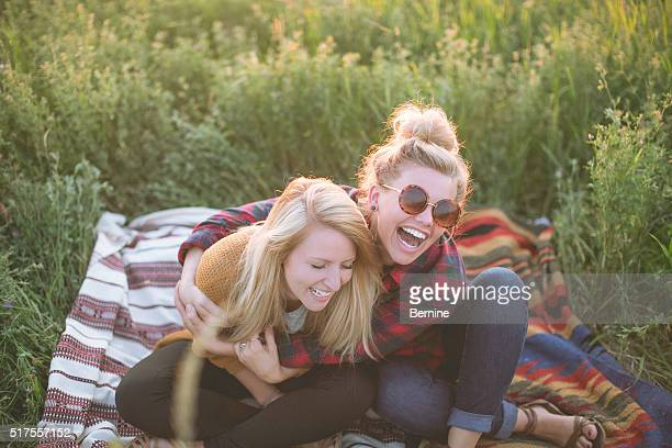 two young adult females sitting in field laughing and hugging - head back stock pictures, royalty-free photos & images