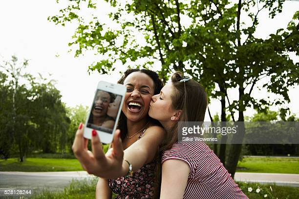 two young adult woman taking a self-potrait with a mobile phone - cheek stock pictures, royalty-free photos & images
