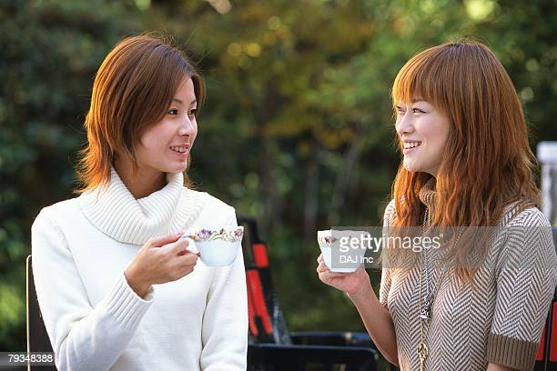 Two Young Adult Women Drinking Tea