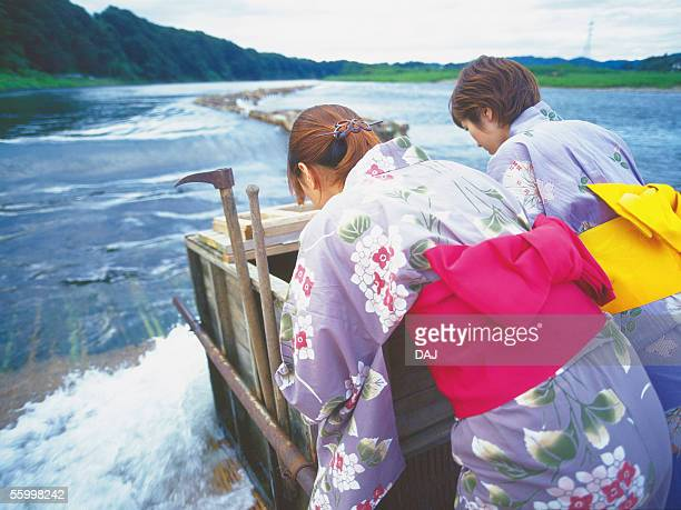 two young adult women standing at weir - obi sash stock pictures, royalty-free photos & images