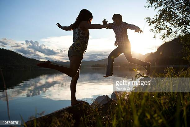Two young adults balancing on rocks at sunset next to the lake.