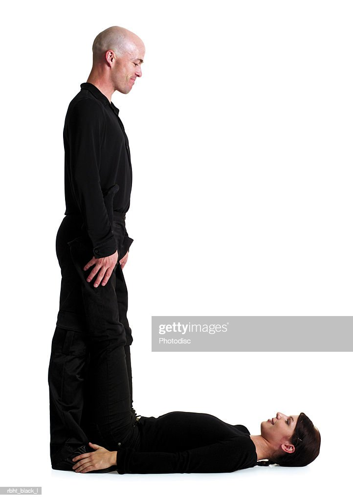 two young adults dressed in black create the letter L : Stockfoto
