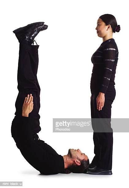 two young adults dressed in black create the letter u - letter u stock photos and pictures