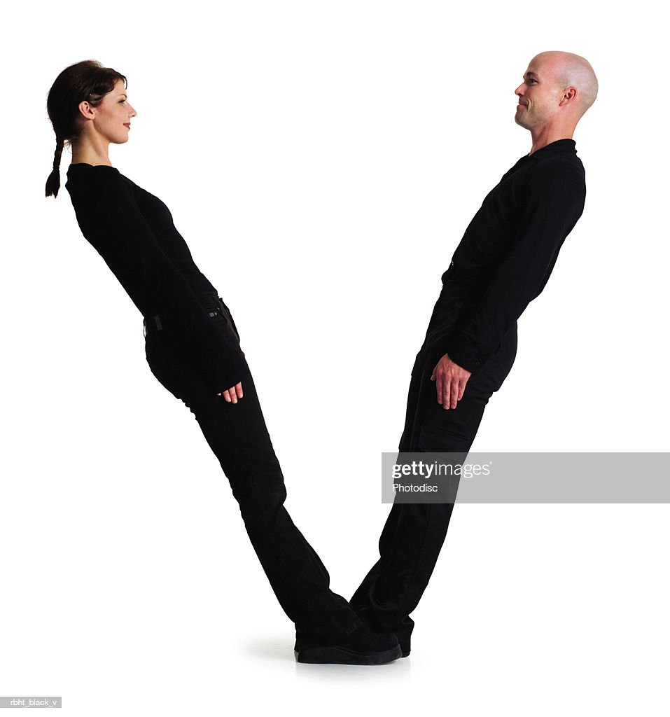 two young adults dressed in black create the letter V : Stockfoto