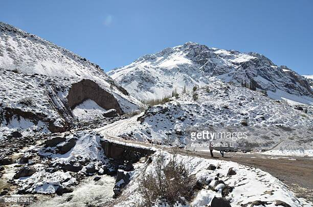 two young adults on the road to el morado glacier. near santiago de chile - tundra stock pictures, royalty-free photos & images