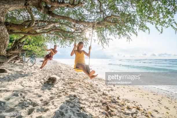 dos jóvenes jugando en columpio en la playa de paraíso tropical, pareja diversión feliz compartiendo bellos momentos en el tiempo de vacaciones en asia - lombok fotografías e imágenes de stock
